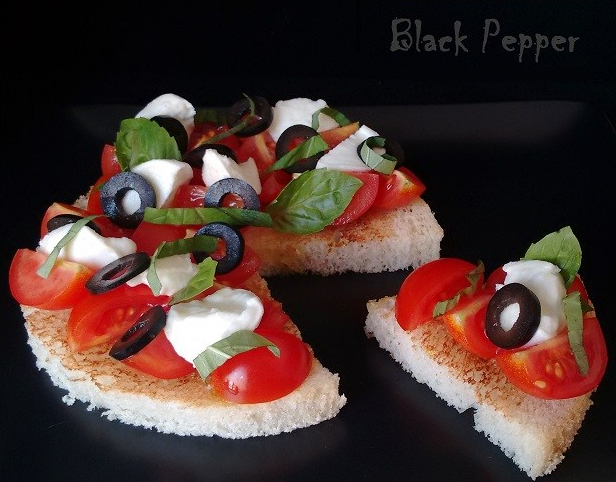 Bruschetta with homemade bread, tomatoes, olives and mozzarella