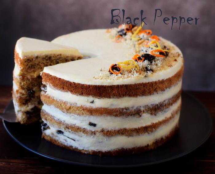 Sponge walnut cake with white chocolate cream and prunes flambé