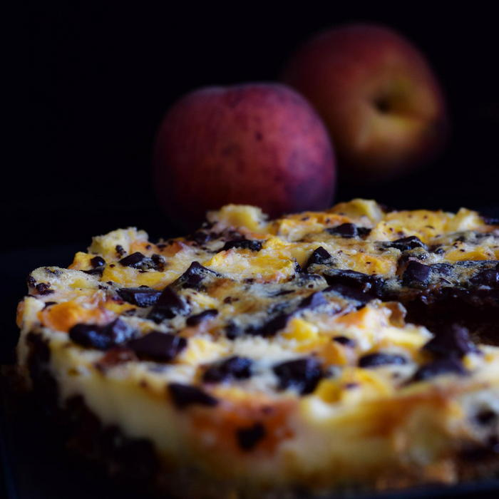 Custard-like milk French pie with peaches and dark chocolate